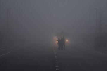 People cross a road in front of a truck in heavy fog in Belfast