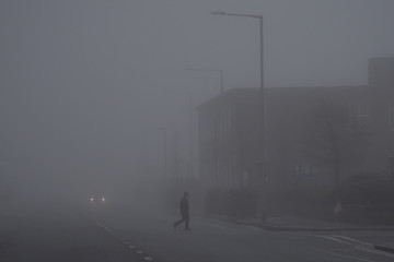 A man walks through heavy fog in Belfast