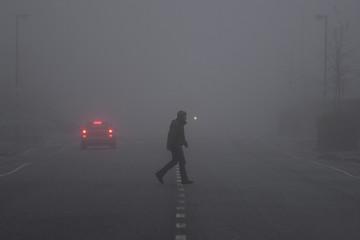 A person walks across a road in heavy fog in Belfast
