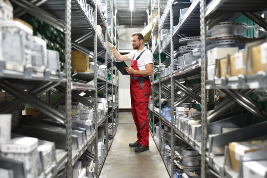 Mitarbeiter im Lager mit KFZ-Ersatzteilen in einer Autowerkstatt // Employees in the warehouse with spare parts for cars in a garage