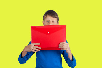 Teenager in blue pullover looking out of red school folder on yellow background
