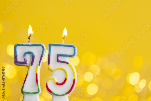 Number 75 Birthday Celebration Candle Against A Bright Lights And Yellow Background