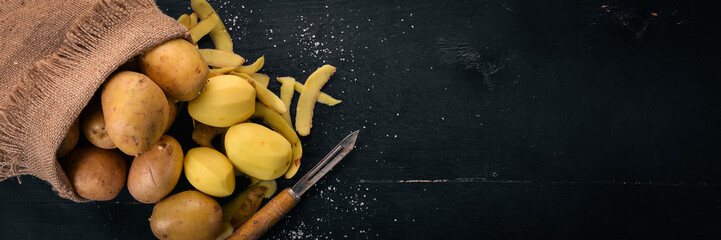 Raw potatoes on a black wooden background. Cooking. Free space for text. Top view.