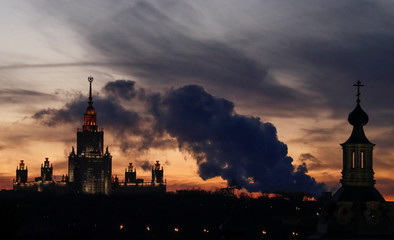 Steam rises from the chimneys of a thermal power plant near domes of the Andreevsky Monastery and the main building of the Lomonosov Moscow State University in Moscow
