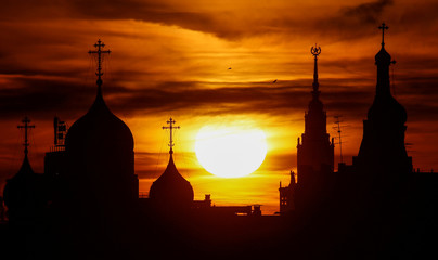 The sun sets over domes of the Andreevsky Monastery and the main building of the Lomonosov Moscow State University in Moscow
