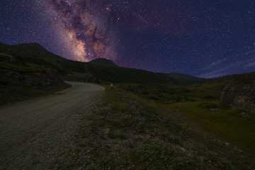 Perspective mountain road leading to the Milky Way