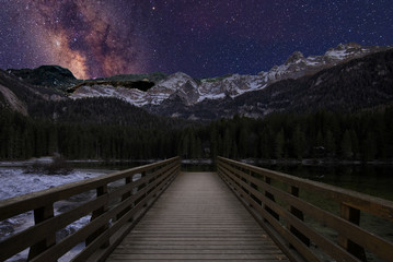 Via Lattea over the snow-covered mountain with a pier in the foreground