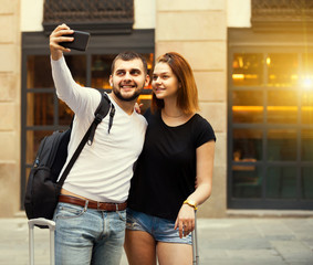 female and male standing with baggage at street and taking selfi