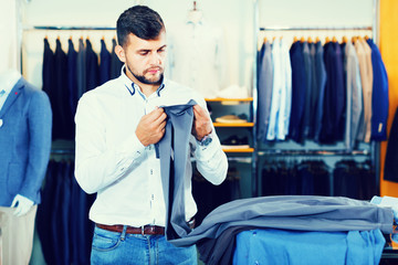 Handsome client choise  pair of pants in fashion store