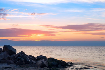 Fotomurais - Seascape. Stones coastal on the background of the sea, horizon with clouds sunset.
