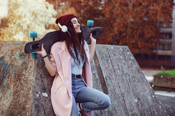 Young urban woman listens to music via headphones and holding longboard