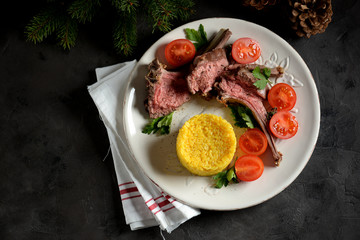 Medium rare rack of lamb with boiled rice and a salad of cherry tomatoes.