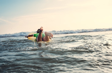 Boy floats on surf board. Beginner surfer, first lessons