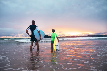Father and son stand on the surf line with surf boards on sunset