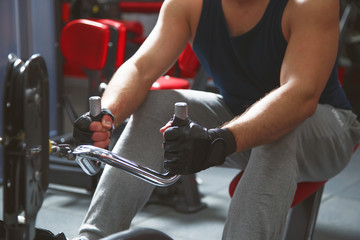Rowing young man in gym training hands close up