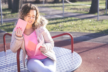 Young beautiful woman reading a love letter on Valentines / Womens Day at the park.