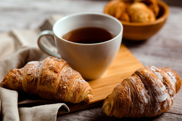 breakfast with tea and croissant on a white wooden background
