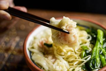 man eating shrimp wonton noodle soup with choy sum