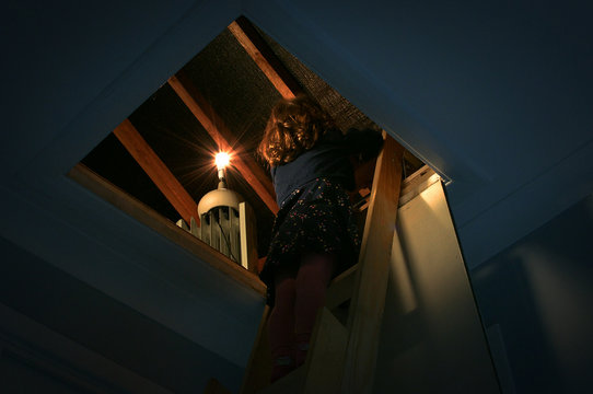 A little girl climbing a ladder into a loft with a single light in it