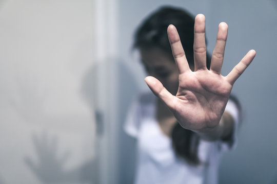 Women abused in her home holding her hand up. Stop sexual harassment against women. Violence and abuse in family relations.