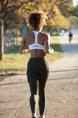 Bare back of woman running is urban jogging path