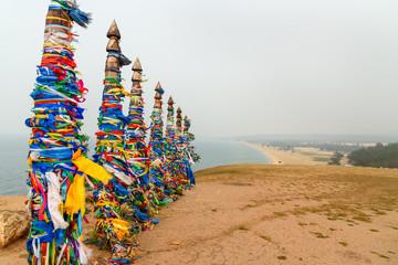 Wooden ritual pillars with colorful ribbons Hadak on cape Burkhan. Lake Baikal. Olkhon Island. Russia
