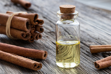 A bottle of cinnamon essential oil with cinnamon sticks on a wooden background