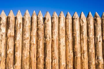 Wooden fence made of sharpened planed logs