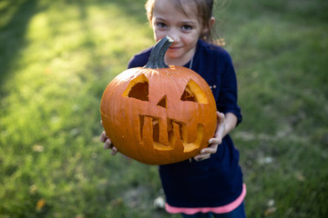Portrait of girl holding jack o lantern while standing on field in yard