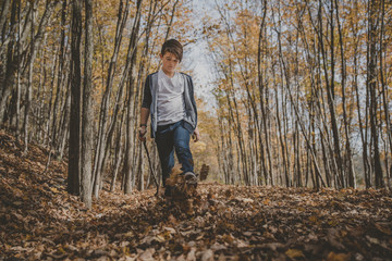 Full length of boy kicking leaves on field during autumn