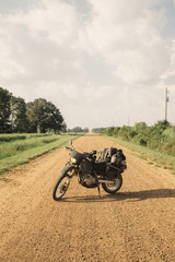 Motorcycle parked on dirt road against sky