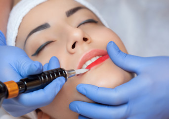 Permanent make-up for red Lips of beautiful woman in beauty salon. Closeup beautician doing  tattooing Lips.