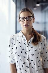 Portrait of confident businesswoman standing by glass door in office