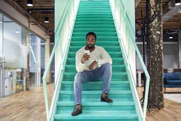 Businessman using mobile phone while sitting on steps in office
