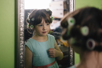 Girl with hair curlers reflecting on mirror while standing at home