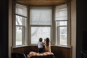 Rear view of siblings kneeling by window at home
