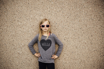 Girl wearing sunglasses standing against wall
