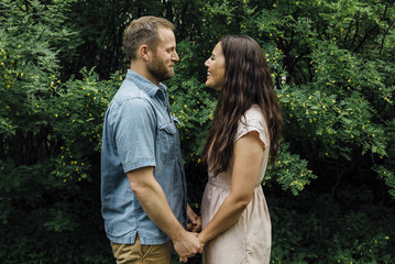 Side view of smiling couple standing against plants