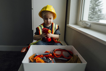 Boy playing with carpentry toys while sitting on table at home