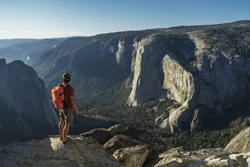 Full length of male hiker standing on cliff at Yosemite National Park
