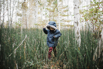 Boy wearing hooded jacket while playing amidst forest