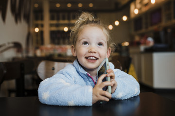 Close-up of smiling girl holding smart phone while sitting at table in restaurant