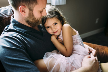 Portrait of girl with father sitting on sofa at home