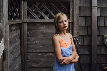 Portrait of girl with towel standing against log cabin