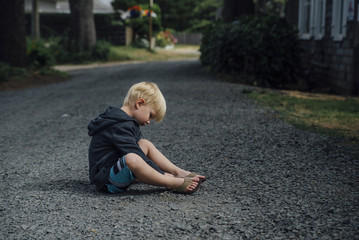 Side view of boy playing with stones while sitting on road