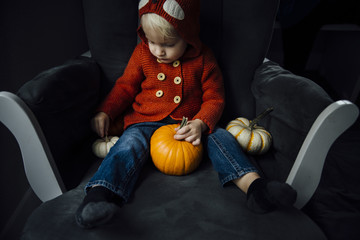 Cute boy playing with pumpkins at home during Halloween