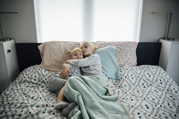 Portrait of sister embracing brother while lying on bed at home