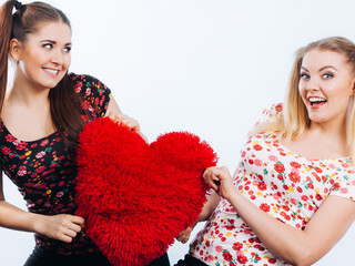 Happy two women holding heart shaped pillow