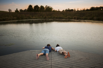 High angle view of siblings lying on pier over lake at park