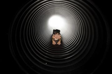 Portrait of playful boy lying in huge metallic pipe